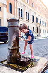 Amused little girl drinks from a nasone