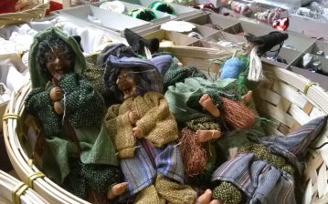 Cesto di vimini contenente bambole della Befana, su un banco a piazza Navona